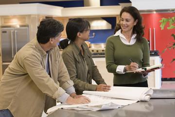 Saleswoman helping customers in kitchen showroom