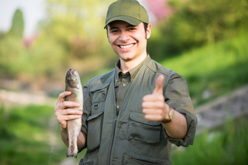 Happy fisherman holding a fish