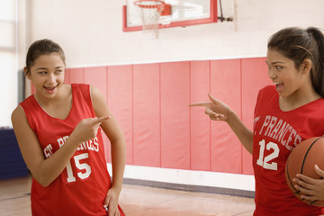 Multi-ethnic girls gesturing in basketball uniforms