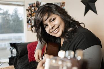 Hispanic girl playing guitar in bedroom
