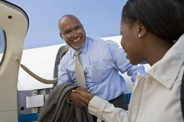 African businesswoman greeting arriving businessman
