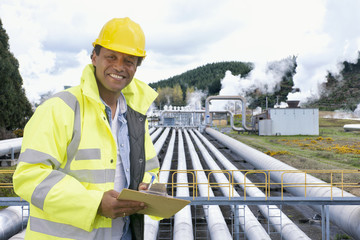 Mixed race worker smiling outside factory
