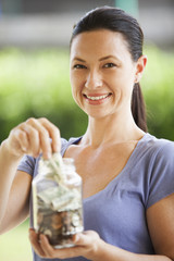 Mixed race woman putting change in jar