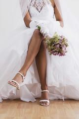 Hispanic bride sitting with legs crossed