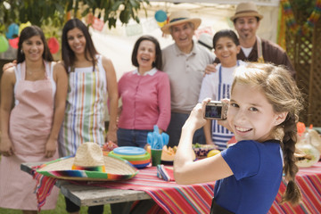Hispanic girl taking photograph of family at barbecue