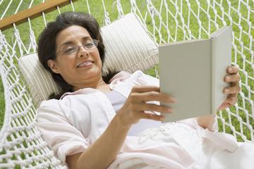 Hispanic woman reading in hammock