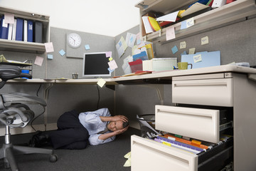 Businessman crying under cubicle desk