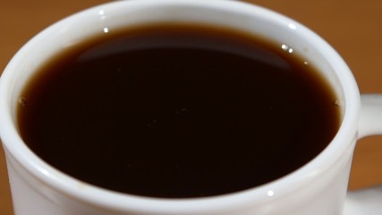 Falling drop into a cup of black coffee, close up