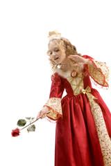 Beautiful little princess using red rose like a magic wand