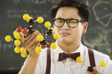 Nerdy Asian male student holding molecular model