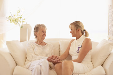 Older Caucasian woman talking with caregiver on sofa