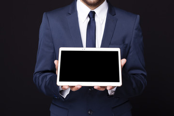Businessman displaying a tablet computer against dark background