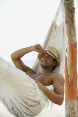 Hispanic man laying in hammock