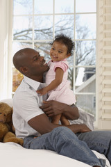 African father holding daughter in bedroom