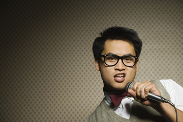 Nerdy Asian man singing into microphone