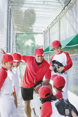 Multi-ethnic boys in baseball uniforms with coach in dugout