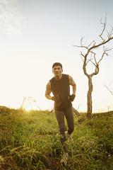 Asian man running in tall grass