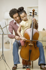 African mother helping daughter play cello