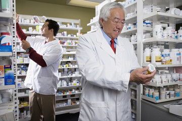 Senior Asian pharmacist reading medication