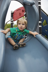 Caucasian boy playing on slide