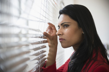 Indian businesswoman peering through blinds in office