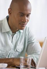 African man looking at laptop