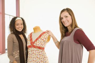 Multi-ethnic women next to dress dummy
