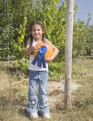 Hispanic girl holding pumpkin with blue ribbon