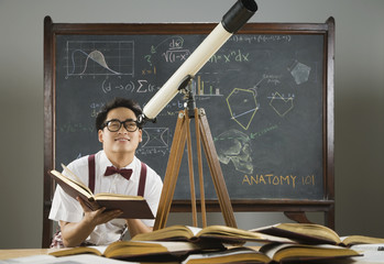 Nerdy Asian male student looking through telescope