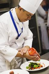 Hispanic male chef garnishing plate of food