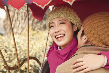 Chinese couple hugging in traditional rickshaw