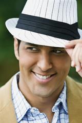Hispanic man adjusting hat