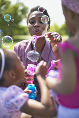 African mother and daughters blowing bubbles