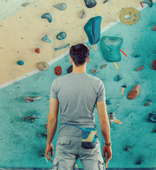 Man standing in front of a practical climbing wall
