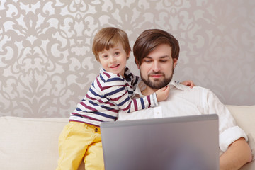 Man and boy use laptop
