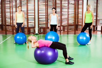 Women exercising in gym, fitness instructor showing exercise