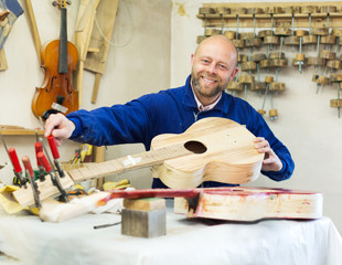 craftsman working with unfinished guitar