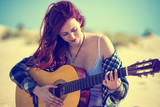 Woman playing guitar on the beach