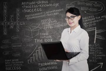 Attractive female student and written blackboard