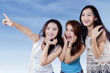 Attractive teenage girls looking at copyspace