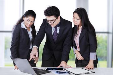 Businessman showing document on laptop