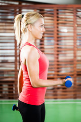 Young woman exercising in gym, using weights