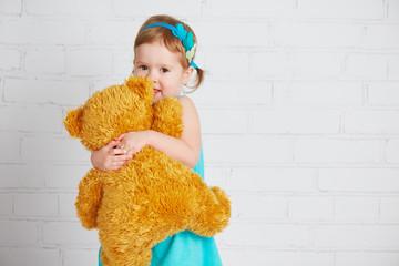 baby girl hugging a loved teddy bear