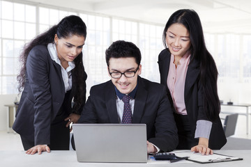 Businessman using laptop with two subordinates