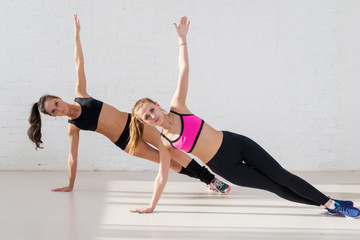 Group of two active sportive women practicing the side plank
