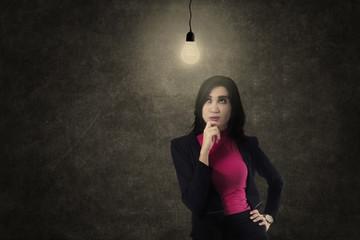 Busineswoman thinking under light bulb