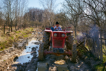 Farmer family driving a tractor on a muddy rural road