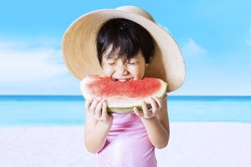 Child eats watermelon on the seaside