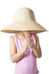 Child with hat eats ice cream in studio