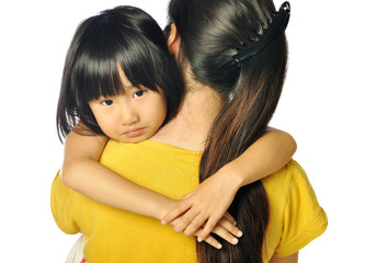 sad asian little girl hugging parent around shoulders
